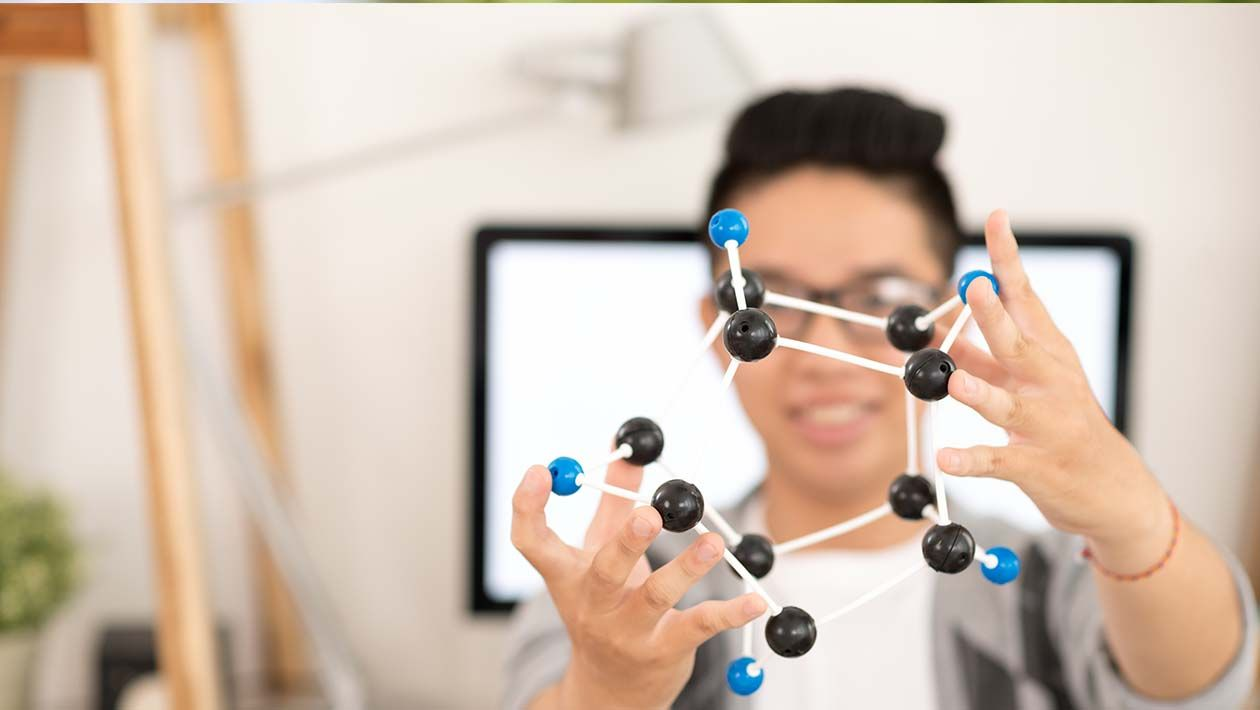 Boy in glasses holding a black and white molecule