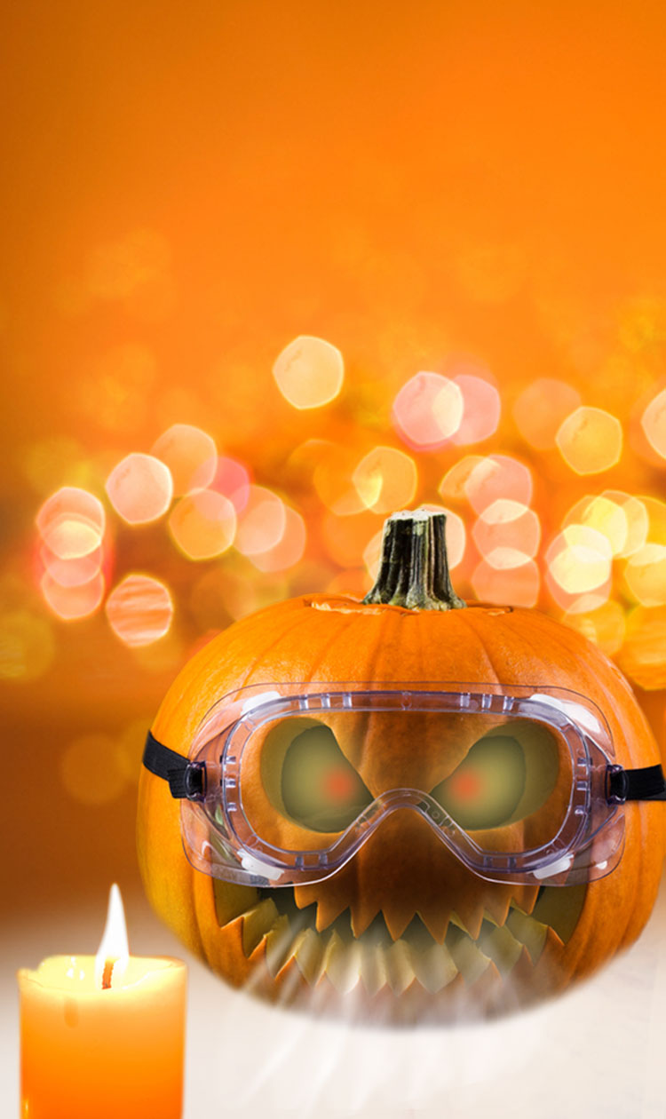 A carved pumpkin wearing goggles with 2 white burning candles next to it.