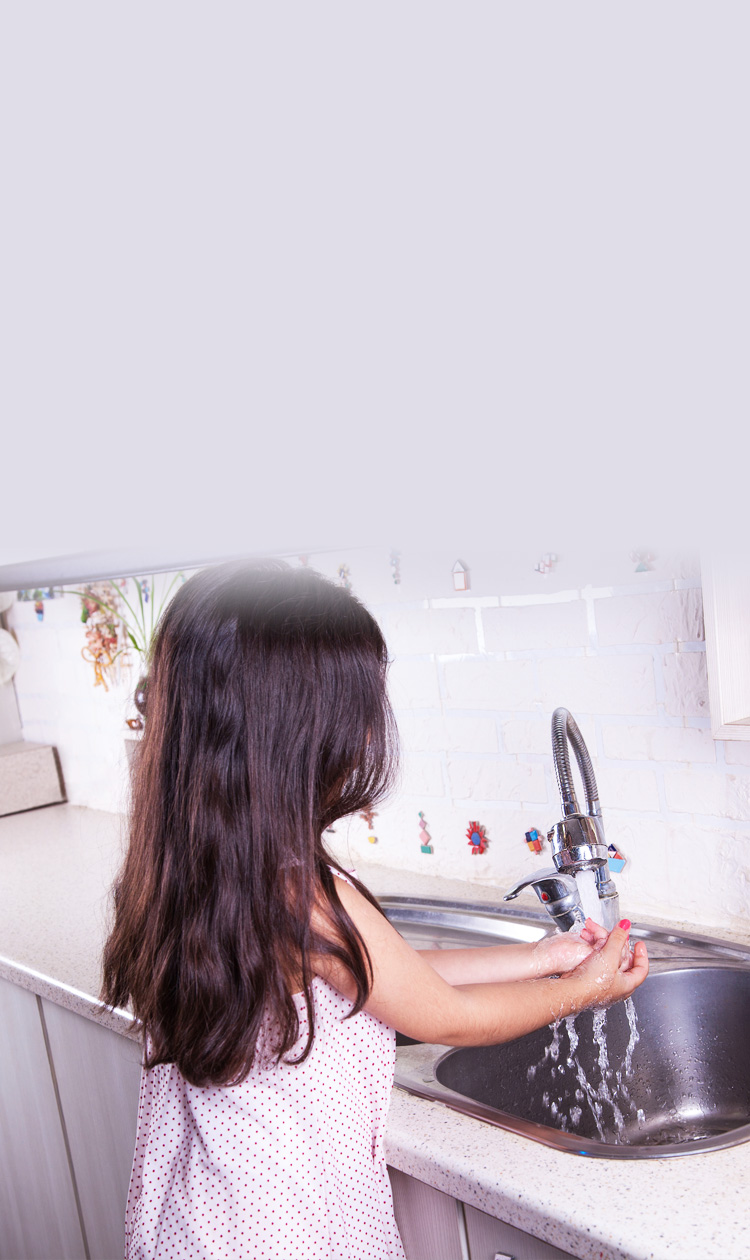 Little girl washing her hands in the kitchen sink to sanitize her hands.