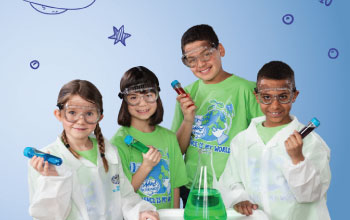 4 kids 2 of which are in lab coats all holding test tubes filled with liquid and one flask with green liquid inside.