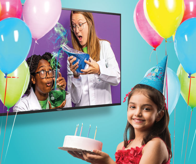 A girl holding a cake wearing a birthday hat watching a tv with a Mad Science instructors pouring a green liquid into a into